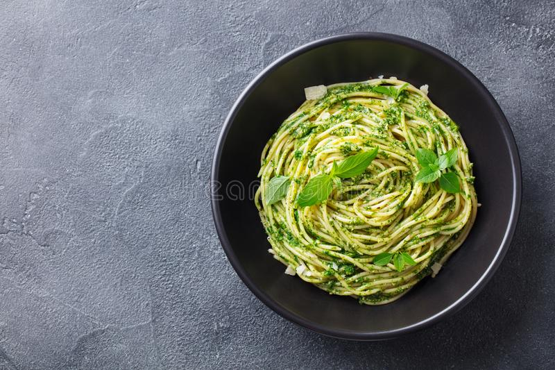 Pasta spaghetti with pesto sauce in black bowl. Grey background. Copy space. Top view. stock images