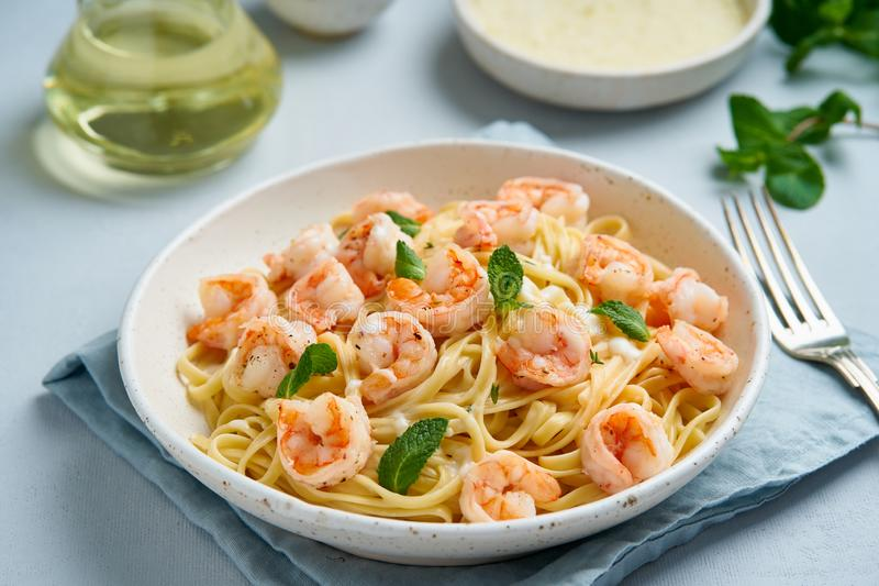 Pasta spaghetti with roasted shrimps, bechamel sauce, mint leaf on blue table, italian cuisine, side view royalty free stock image