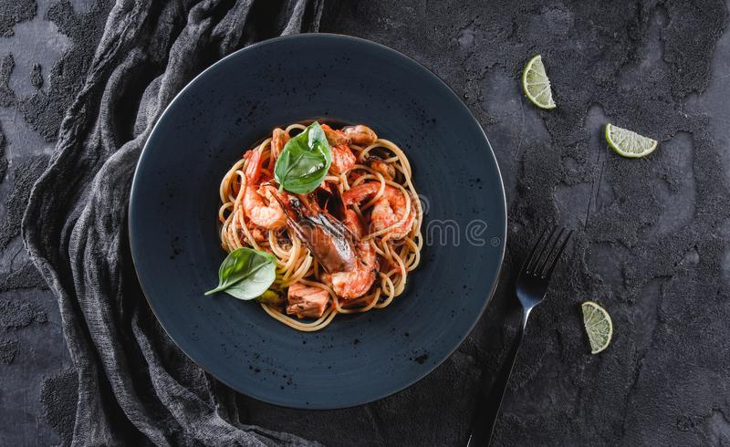 Pasta spaghetti with seafood, langoustine, mussels, oysters, shrimp, salmon fillet in sauce with herbs in plate over dark grey. Background. Italian food, top stock photo