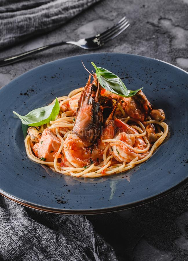 Pasta spaghetti with seafood, langoustine, mussels, oysters, shrimp, salmon fillet in sauce with herbs in plate over dark grey. Background. Italian food, top stock photography