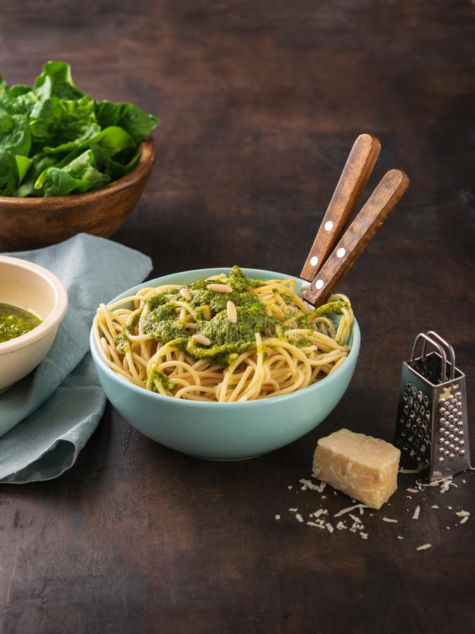 Pasta spaghetti with spinach pesto sauce, walnut and fresh raw spinach leaves in bowl. dark background. Healthy eating, vegetarian stock photography