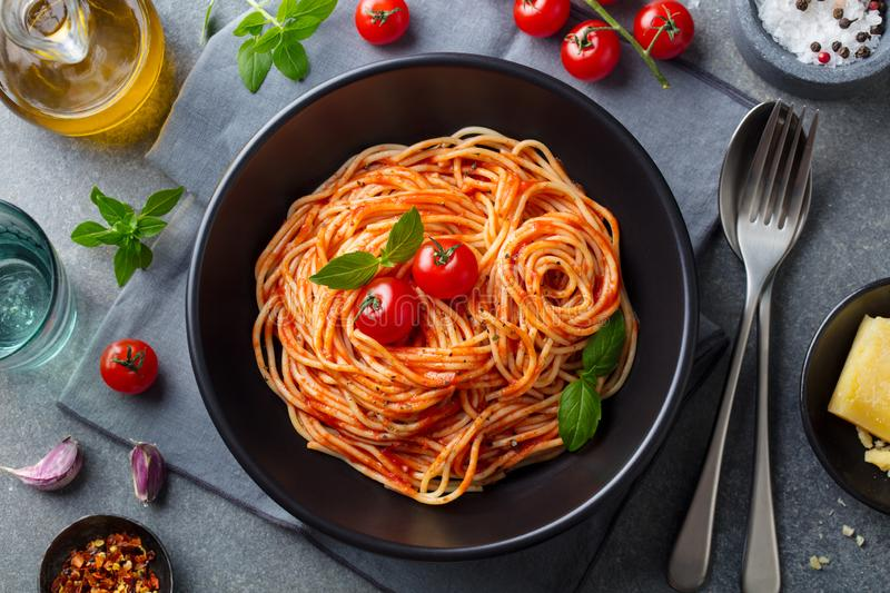 Pasta, spaghetti with tomato sauce in black bowl on grey stone background. Top view. stock image