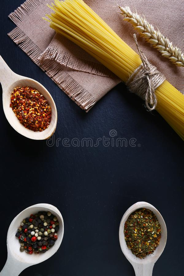 Pasta spaghetti, wheat spikes, on a napkin, wooden spoons with spices, background of food ingredients, image of the concept of adv royalty free stock images