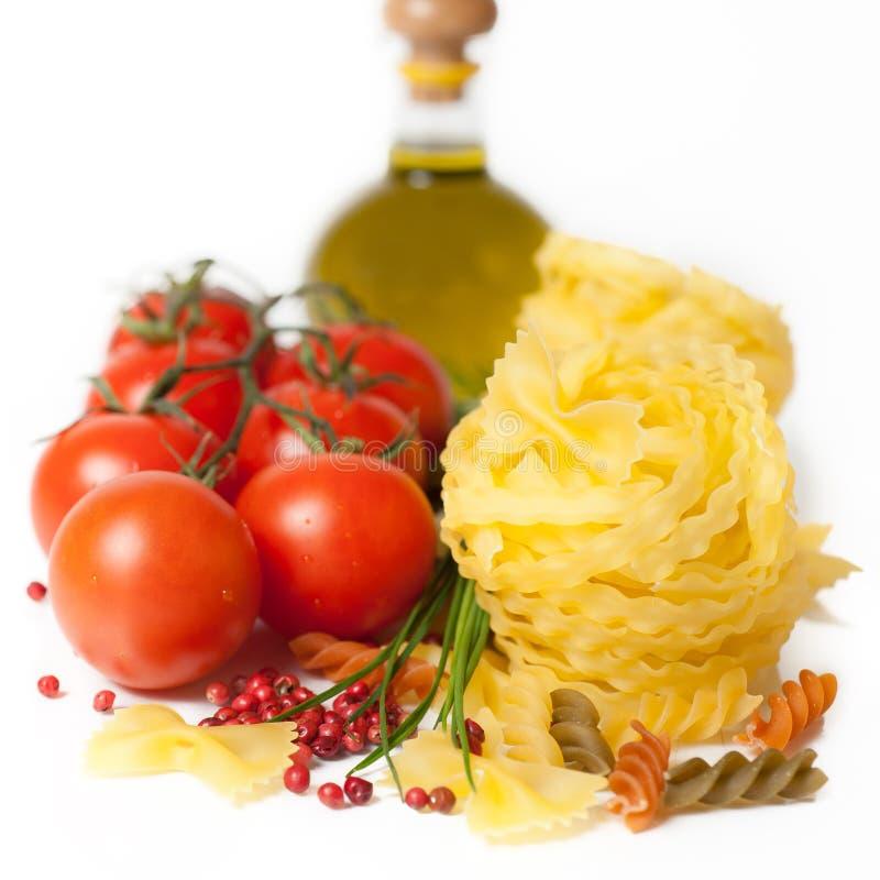 Pasta, spezie e pomodori italiani su una parte posteriore di bianco immagini stock