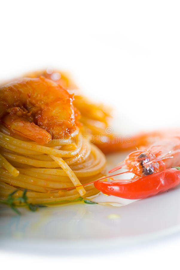 Pasta and spicy shrimps. Italian spaghetti pasta and fresh spicy shrimps sauce over white stock photos