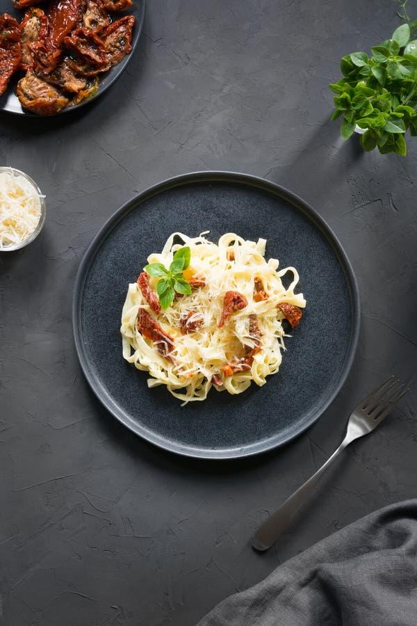 Pasta tagliatelle with dried tomatoes and oregano on black. Delicious Mediterranean lunch. Pasta tagliatelle with dried tomatoes and oregano on black concrete stock photography
