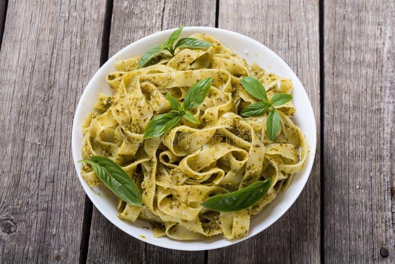 Pasta tagliatelle with green sauce pesto . Italian food background. Pasta tagliatelle with green sauce pesto Italian food background stock photo