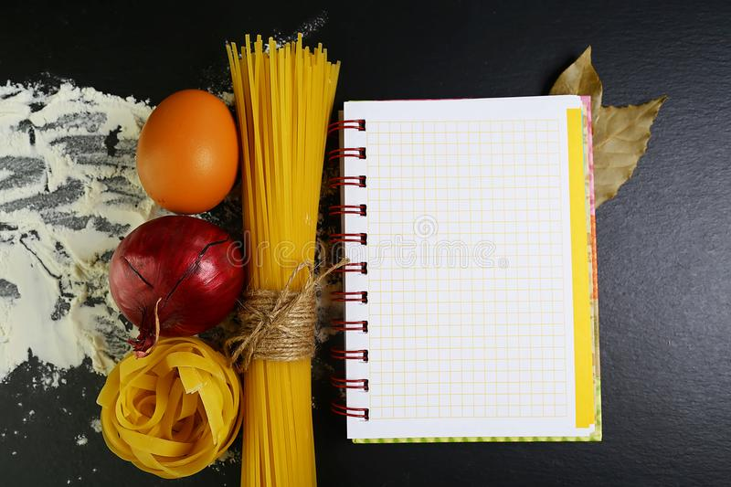 Pasta tagliatelle, spaghetti, italian foods concept and menu design, onion bay leaf, raw eggs and flour on a shale board, empty sp royalty free stock image