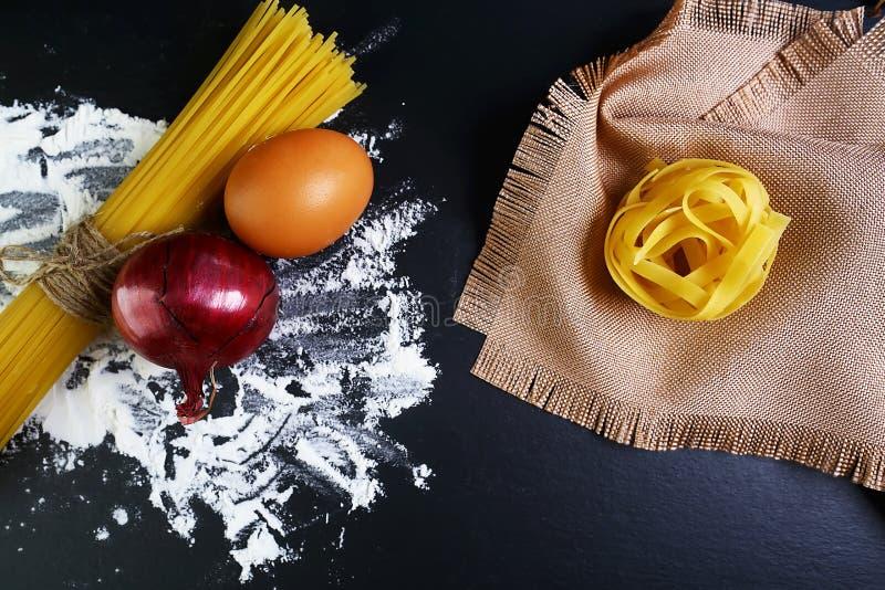 Pasta tagliatelle, spaghetti, italian foods concept and menu design, onion bay leaf, raw eggs and flour on a shale board, napkin t stock photos