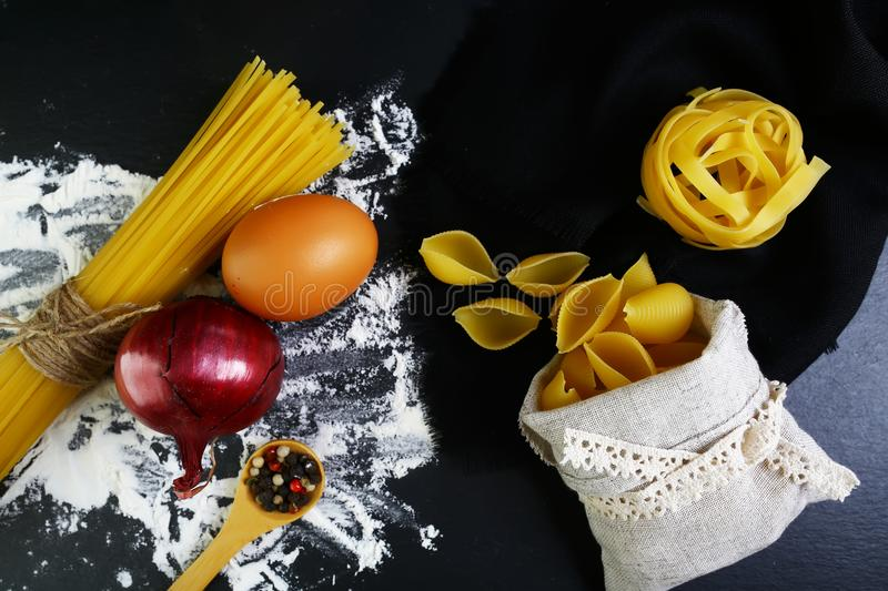 Pasta tagliatelle, spaghetti, italian foods concept and menu design, spices on wooden spoon, shells in a bag, raw eggs and flour o stock images