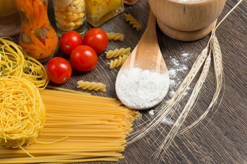Pasta, tomater och mjöl på skeden royaltyfria foton