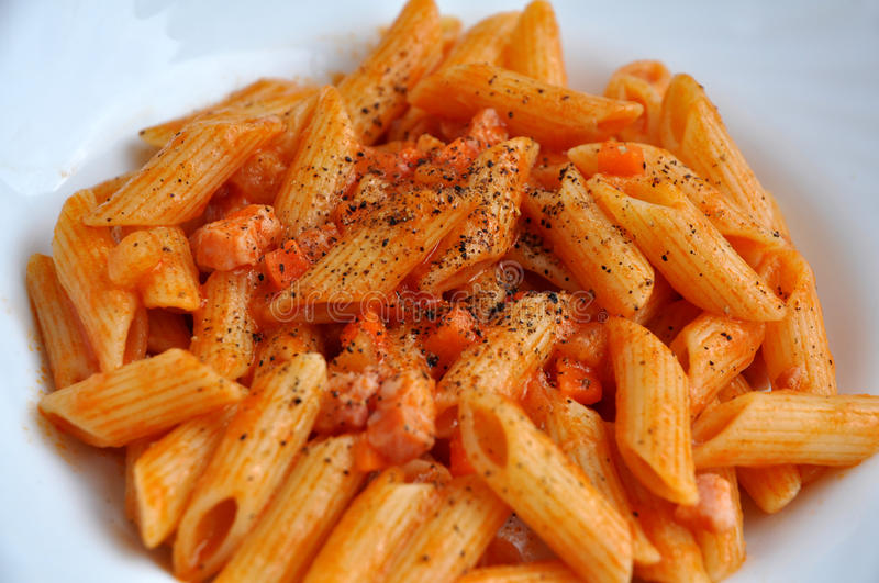 Pasta and tomato. Short pasta dressed with tomato sauce bacon and black pepper stock photos