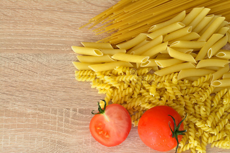 Pasta and tomato. Pasta, spaghetti, penne with tomatoes royalty free stock photo