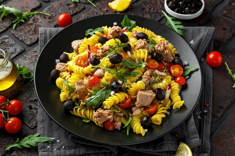 Pasta Tuna salad with tomatoes, wild rocket, black olives and red onion.  royalty free stock photos