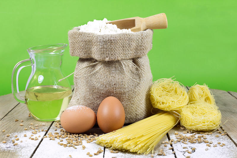 Pasta, Two Eggs, Jute Bag Filled with Flour, Wooden Spoon and Olive Oil in Glass Bottle on an Old Wooden Table stock photography