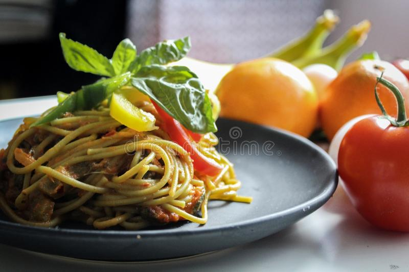 Pasta With Vegetable Dish on Gray Plate Beside Tomato Fruit on White Table royalty free stock image