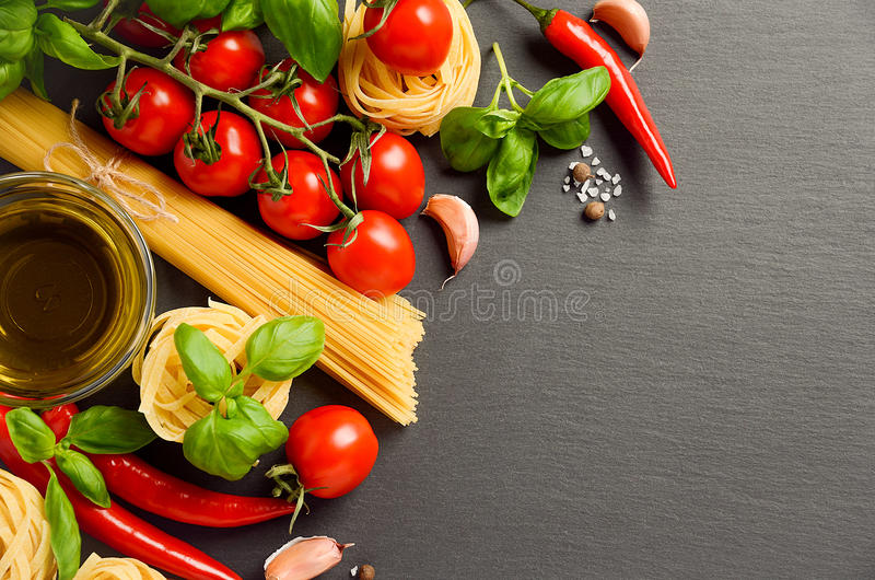 Pasta, vegetables, herbs and spices for Italian food on black background. Top view, copy space stock photos
