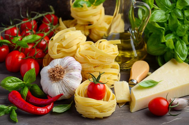 Pasta, vegetables, herbs and spices for Italian food on the wooden background royalty free stock image