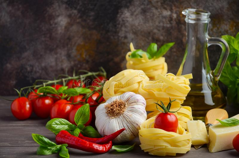 Pasta, vegetables, herbs and spices for Italian food on the wooden background stock image
