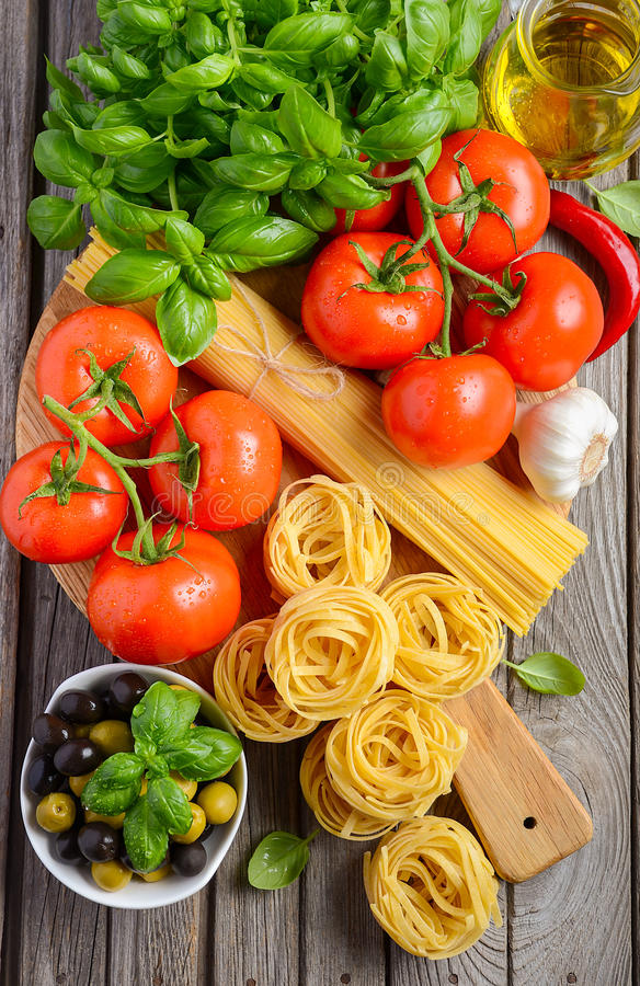 Pasta, vegetables, herbs and spices for Italian food on wooden background royalty free stock photography