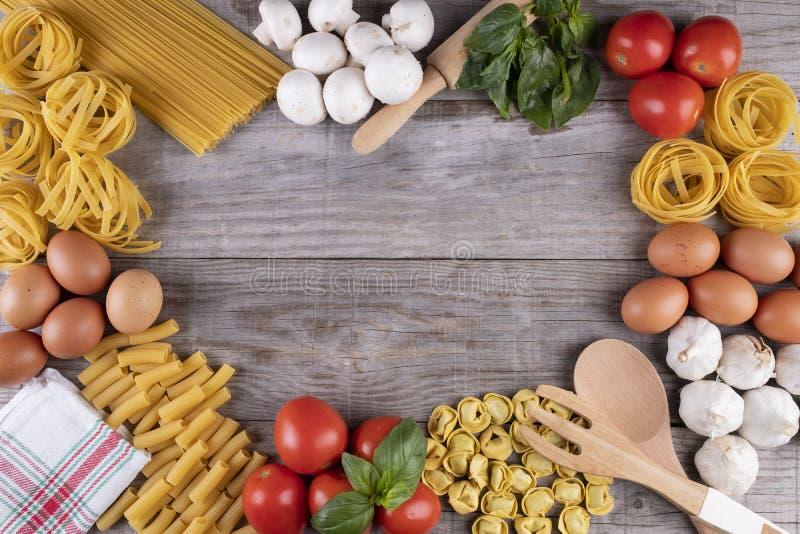 Pasta, verdure, uova, sul bordo di legno, ingredienti per il ristorante italiano fotografia stock libera da diritti