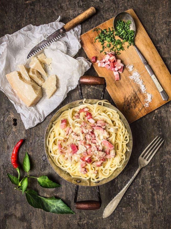 Pastacarbonara i vintagenpanna med parmesanost, kryddor och örter på skärbräda royaltyfria foton
