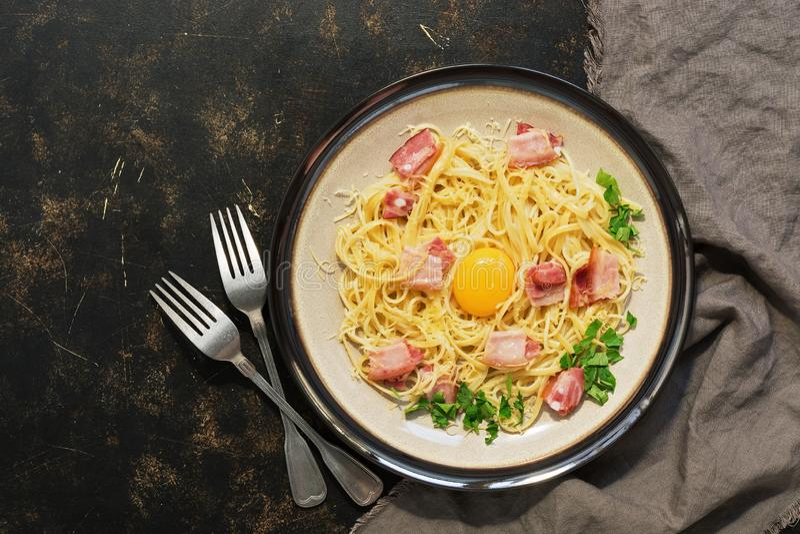 Pastacarbonara med parmesan, bacon, rå äggula på en mörk lantlig bakgrund ovanför sikt royaltyfri bild