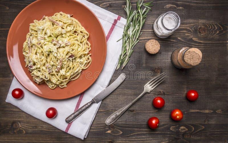 Pastacarbonara med zucchinin, i en brun platta med den tappningkniven och gaffeln, med örter och kryddor på lantlig träbakgrundsö royaltyfria foton