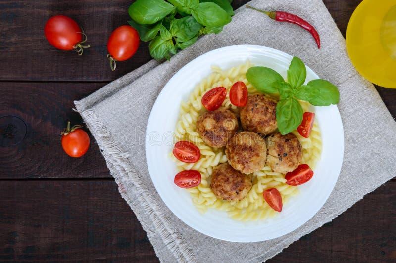 Pastafutsilli med köttbollar, körsbärsröda tomater, basilika på en vit platta på en mörk träbakgrund royaltyfria bilder