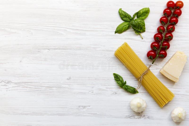 Pastaingredienser: spagetti, ostparmesan, vitlök och tomater med basilika på vit träbakgrund, royaltyfri foto