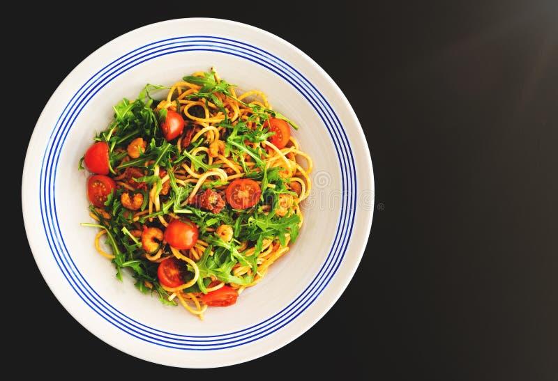Pastaplatta med spagetti med scampi, rucola och torkad nya tomater arkivfoto