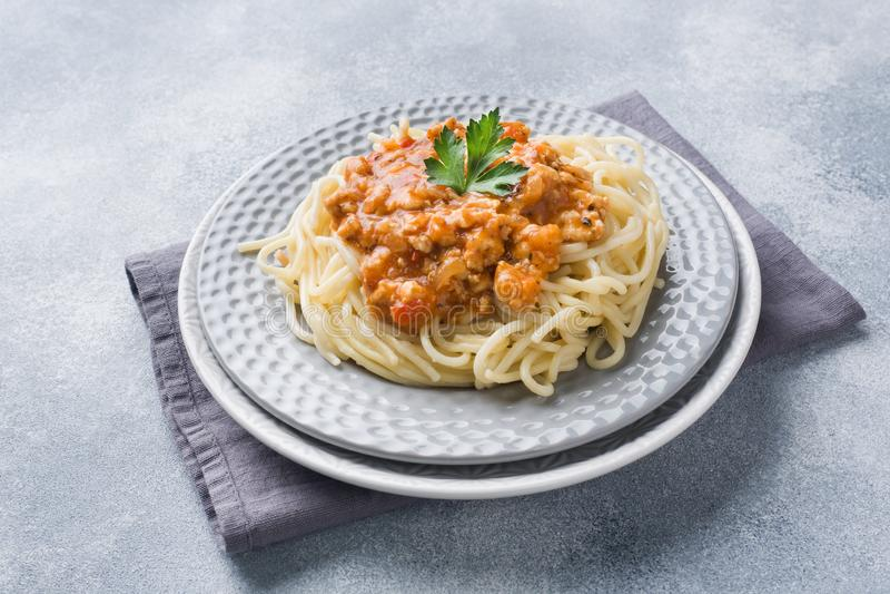 Pastas boloñés de los espaguetis en la placa blanca, tabla gris fotos de archivo