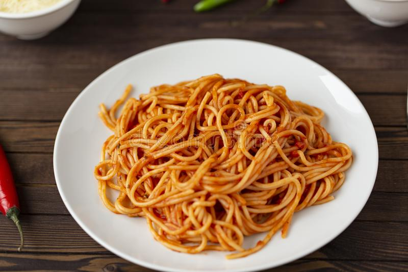 Pastas boloñesas de los espaguetis con la salsa de tomate y carne picadita, queso parmesano rallado y albahaca fresca fotografía de archivo libre de regalías