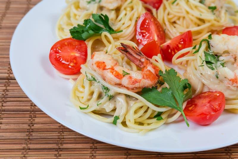 Pastas cocinadas de los espaguetis con el primer de las colas del camarón y de los tomates de cereza fotografía de archivo libre de regalías