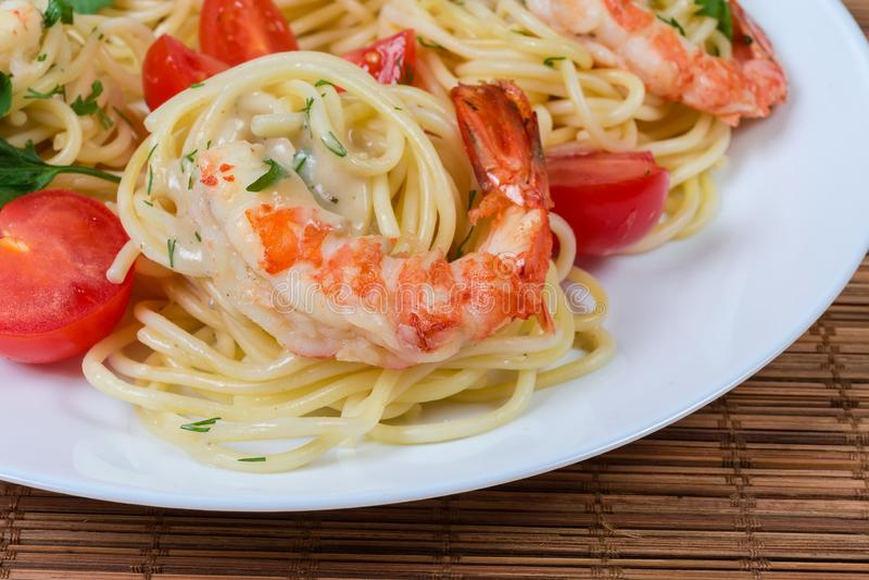 Pastas cocinadas de los espaguetis con el primer de las colas del camarón y de los tomates de cereza imagen de archivo
