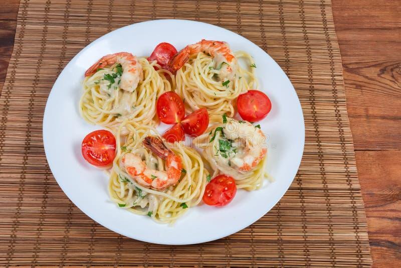 Pastas cocinadas de los espaguetis con las colas del camarón y los tomates de cereza imagen de archivo libre de regalías