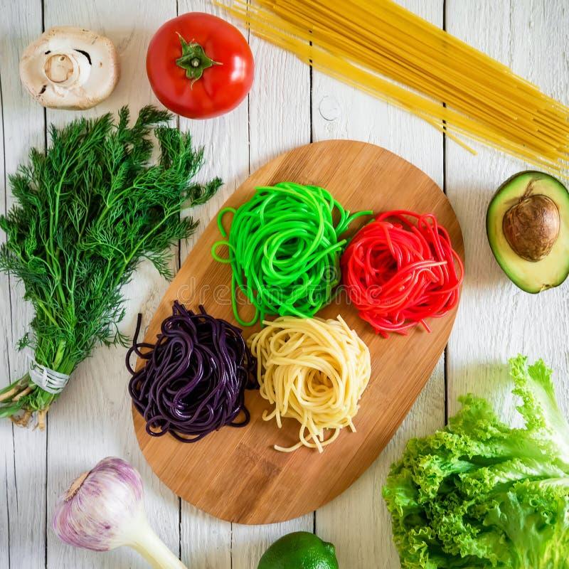 Pastas coloridas en una placa y verduras crudas en el fondo de madera blanco Endecha plana Visión superior Alimento asiático fotos de archivo