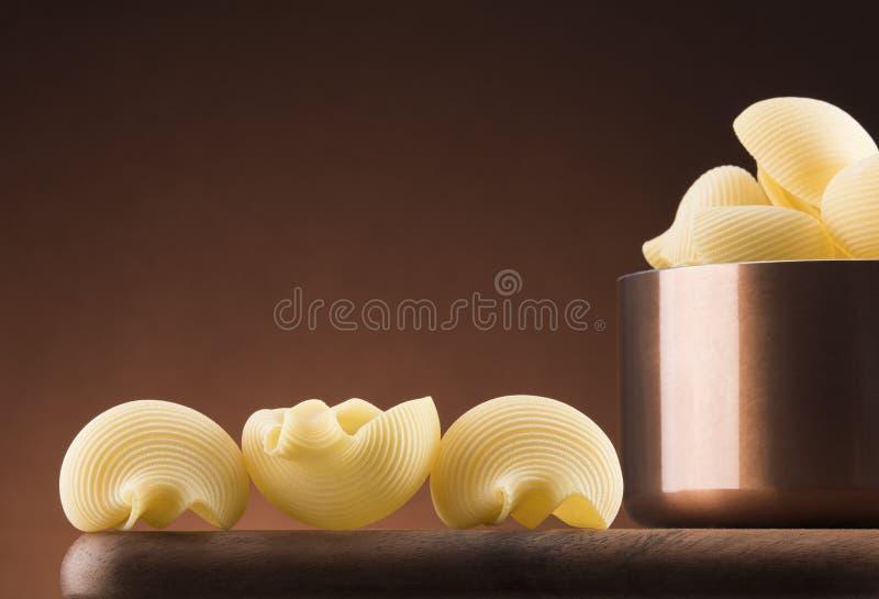Pastas con el pote de cobre en un fondo ligero fotografía de archivo