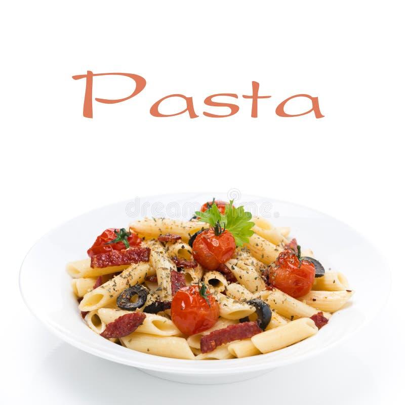 Pastas con la salchicha, los tomates de cereza y las aceitunas en la placa imagen de archivo libre de regalías