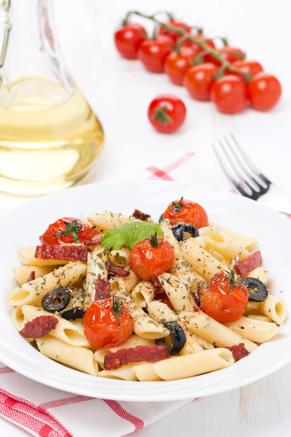 Pastas con la salchicha, los tomates de cereza y las aceitunas, verticales fotos de archivo libres de regalías