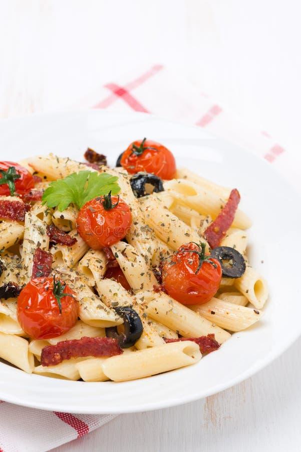 Pastas con la salchicha, los tomates y las aceitunas, verticales imagenes de archivo