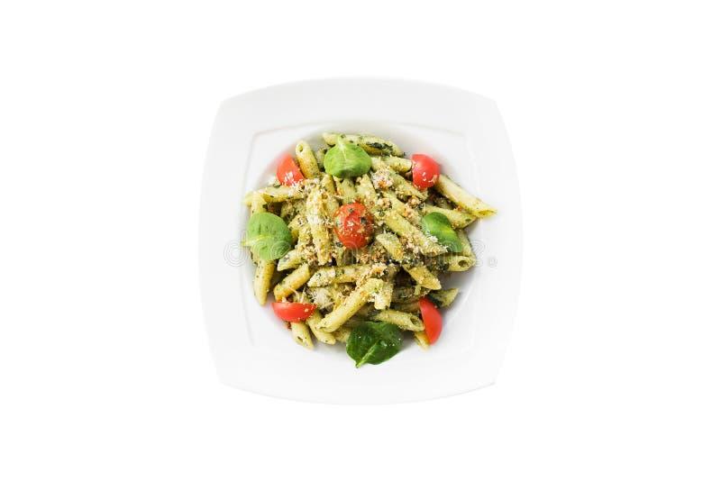 Pastas con la salsa del pesto, la albahaca fresca y las nueces en la placa blanca Espagueti aislado en el fondo blanco imagenes de archivo