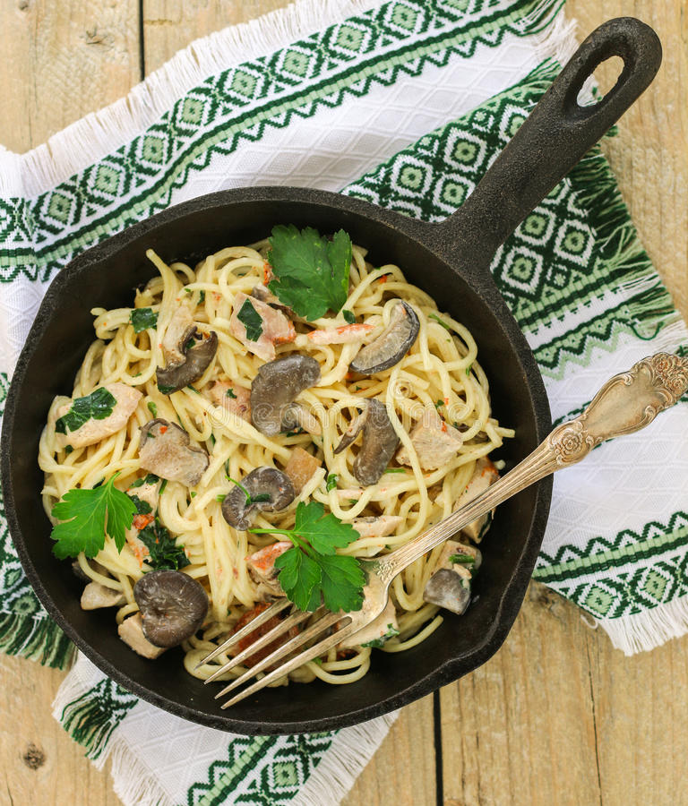 Pastas con las setas y la carne en una salsa cremosa Espaguetis, setas de ostra, pollo y perejil imagen de archivo