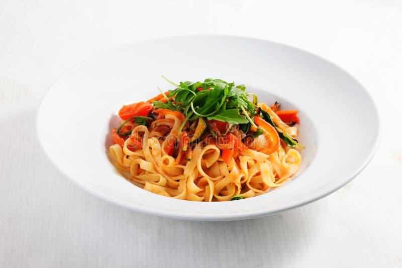 Pastas con las verduras, tomates, calabacín, pimientas, aisladas en el menú redondo blanco de la placa de la salsa de tomate del  imagen de archivo libre de regalías