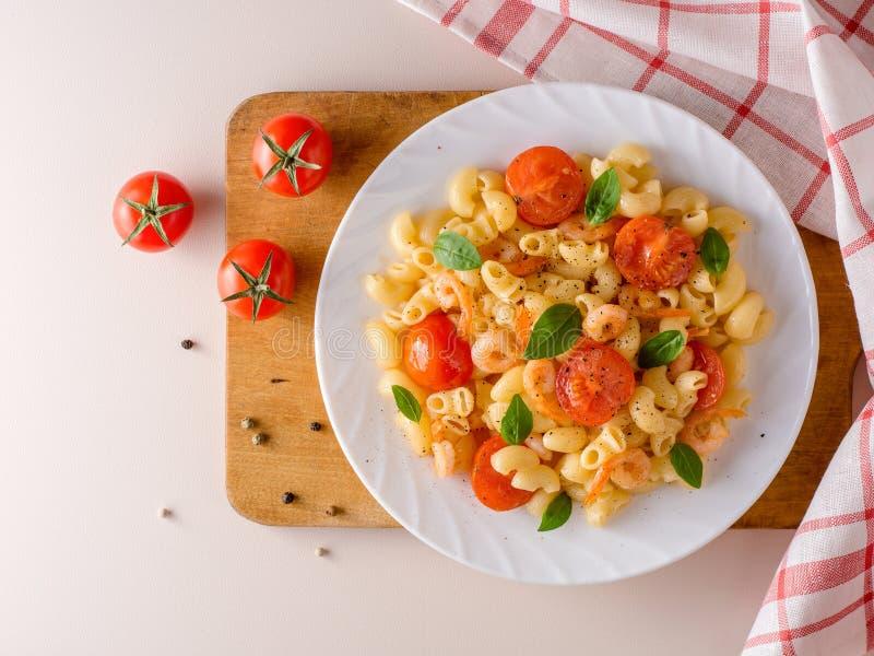 Pastas con los camarones, los tomates de cereza y la albahaca en la placa blanca fotografía de archivo libre de regalías