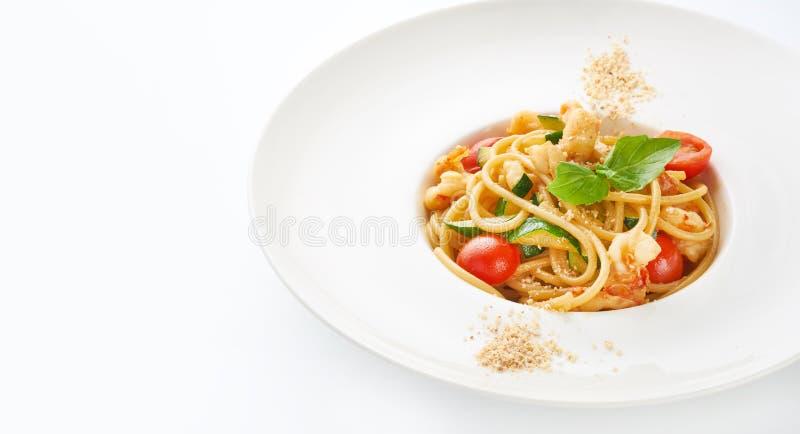 Pastas con los camarones, los tomates de cereza, el calabacín y la albahaca en el fondo blanco imágenes de archivo libres de regalías