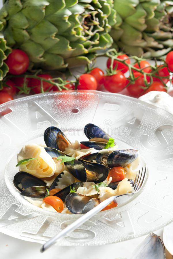 pastas con los mejillones, las alcachofas y los tomates de cereza imagen de archivo