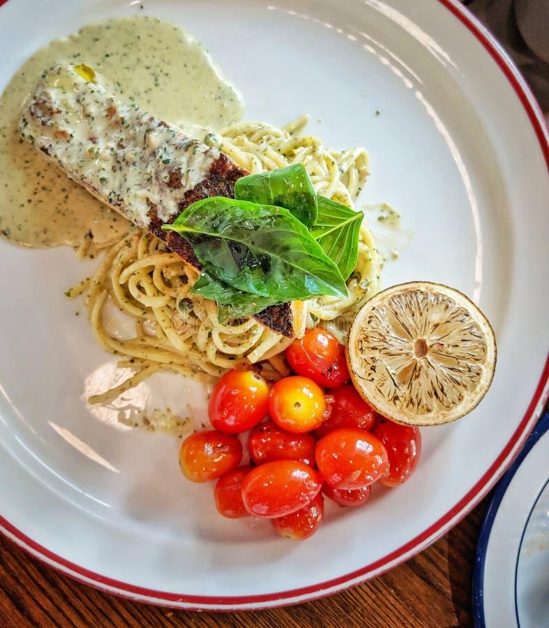 Pastas cremosas deliciosas con los salmones asados a la parrilla en el top fotos de archivo