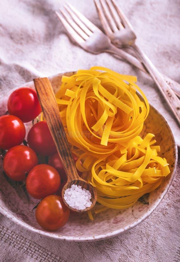 Pastas crudas de los tallarines con los tomates de cereza imágenes de archivo libres de regalías