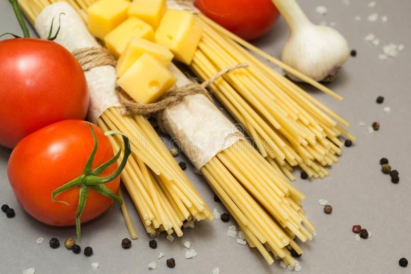 Pastas crudas en un fondo gris en un paquete rústico Tomates, ajo, pimienta y sal imagen de archivo libre de regalías